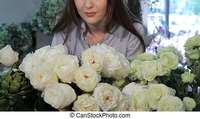 Female florist looks at white roses at flower shop