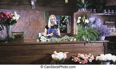 Female florist making bouquet at flower shop