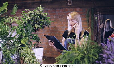 female florist on the phone orders flowers from the supplier...