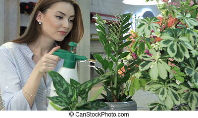 Female florist sprays water on houseplants at flower shop