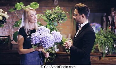 female florist talking with the buyer in the flower shop -...