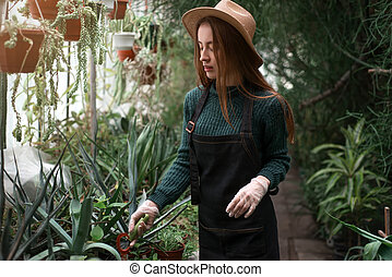 Female florist with shovel in hands