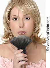 Female flowing excess powder from makeup brush - A female...