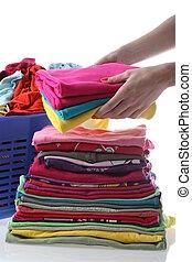Female folds laundry - Female folding children's clothes on...