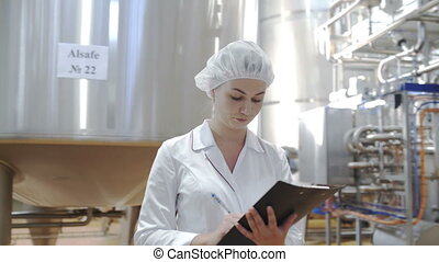 Female Food factory worker monitors production and takes...