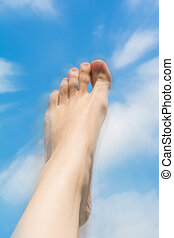 Female foot close up against the sky.