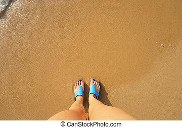 female foot in flip flops on the beach