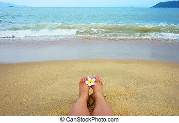 female foot on the beach, flower