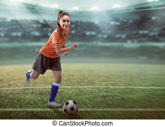 Female football player dribbling ball