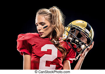 Female football player posing with helmet