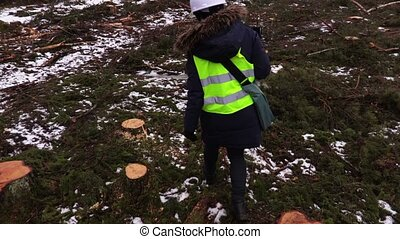 Female forestry inspector checking felling site