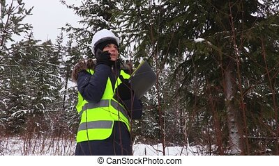 Female forestry worker using smart phone in woods