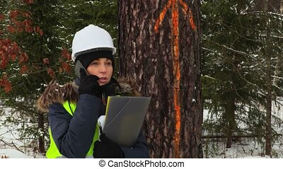 Female forestry worker using smart phone near marked tree