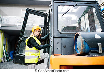 Female forklift truck driver outside a warehouse.