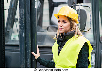 Female forklift truck driver outside a warehouse. A woman...