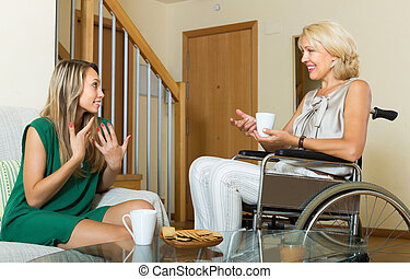Female friend visiting disabled woman
