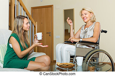 Female friend visiting disabled woman - Female friend...