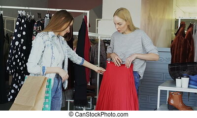 Female friends are shopping together. They are standing beside rails with women's clothes, taking pleated skirt, looking at it carefully and fitting it while chatting and smiling
