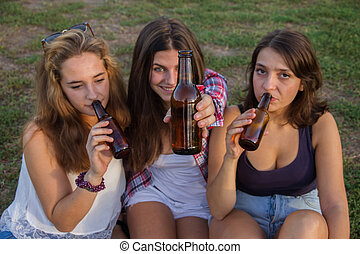 Female friends celebrating the holiday having a good time drinking beer in a park. They're happy.