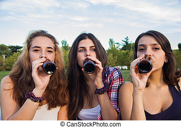 Female friends celebrating the holiday having a good time drinking beer in a park.