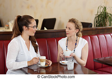 Female friends chatting in a cafe