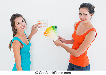 Female friends choosing color for painting a room