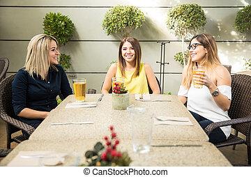 Female friends drinking in a terrace