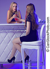 Female friends enjoying cocktails in a nightclub