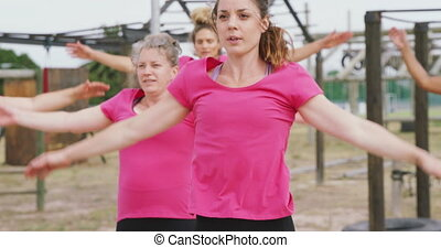 Front view of a happy multi-ethnic group of women enjoying exercising at boot camp together, wearing pink t shirts and doing jumping jacks, in slow motion