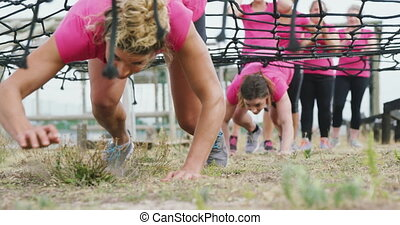 Low angle front view of two happy Caucasian women wearing pink t shirts enjoying exercising at boot camp together, crawling under a net, while other women wait for their turn in the background, in slow motion