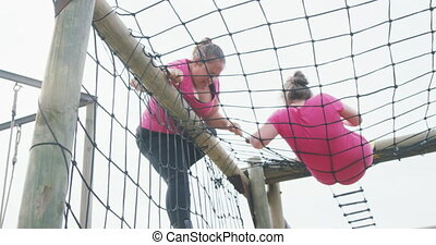 Low angle side view of a Caucasian and a mixed race woman enjoying exercising at boot camp together, climbing on nets over a climbing frame, in slow motion
