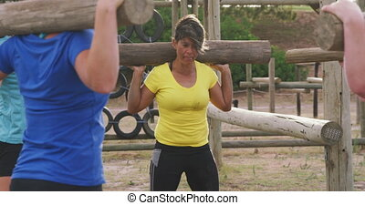 Side view of a happy multi-ethnic group of female friends enjoying exercising at boot camp together, standing in a circle doing squats with wooden posts on their shoulders in slow motion