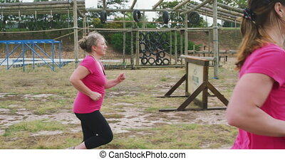 Female friends enjoying exercising at boot camp together - ...