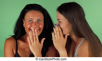 Female friends gossiping on green chromakey background -...