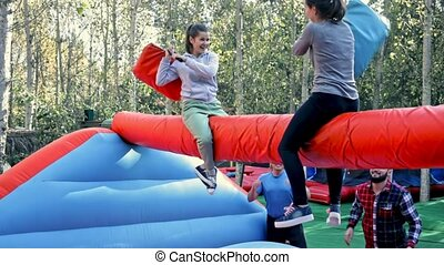 Female friends having funny wrestling by pillows on inflatable beam in outdoor amusement park