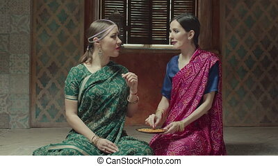Female friends in sari tasting fragant indian dish - Seated...
