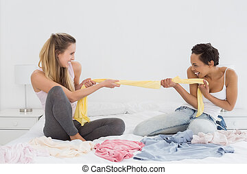 Female friends jokingly fighting over clothes on bed