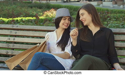 Female friends laugh on the bench