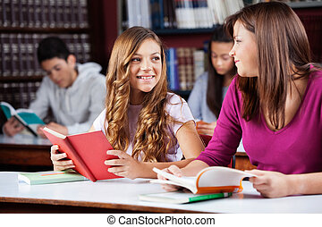 Female Friends Looking At Each Other While Studying In Library