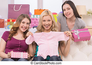 Female friends on Baby Shower. Happy young women holding baby clothes and gift boxes while smiling at camera