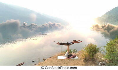 Female friends performing yoga against river and mountain -...