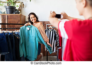 female friends photographing at clothing store