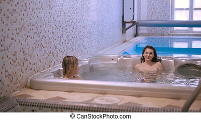 Female friends relaxing in jacuzzi and speaking in 4K