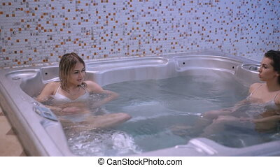 Female friends relaxing in jacuzzi, speaking