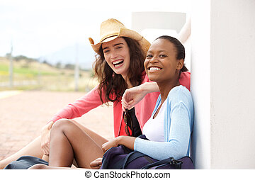 Female friends sitting at railway station