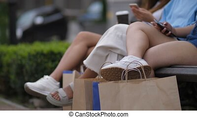 Female friends sitting outdoors with shopping bags