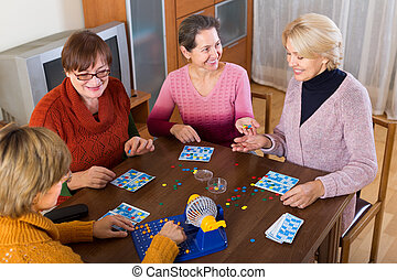 female friends sitting with lotto - Positive senior female...