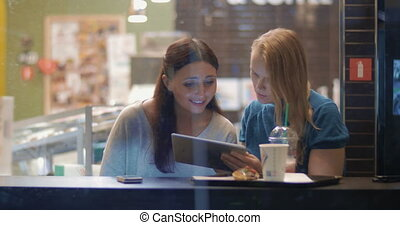 Female friends talking and using touch pad in cafe