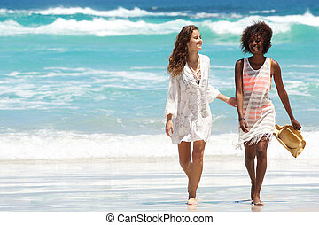 Female friends walking barefoot by the water on a beach