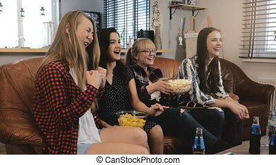 Female friends watch comedy film at home on TV. Happy girls...